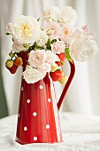 Summer bouquet of white garde roses & sprigs of strawberries in red enamel jug
