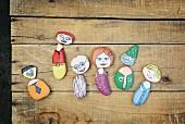 Bemalte Steine mit lustigen Menschenmotiven auf rustikaler Holzunterlage