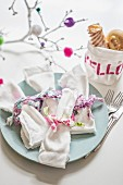 Fabric remnants used as decorative ribbons for linen napkins in front of hand-made fabric bread bag decorated with motto 'HELLO'