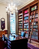 Traditional bookcase with library ladder behind heavy desk