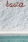 Detail einer weißen Wand mit Schritzug basta