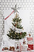 Picture of Christmas tree on wall with wrapped gifts below
