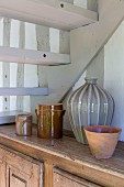 Stoneware pots on top of cabinet below staircase