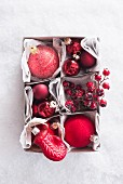 Box of red Christmas baubles (top view)