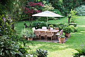 Seating area below parasol in neat garden