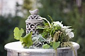 Flower arrangement of orchids & grapes on small table outdoors