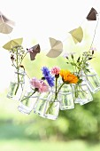 Paper garland and garland of small glass bottles holding summer flowers