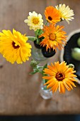 Yellow pot marigolds in glass vase on shabby-chic wooden table