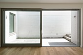 View into simple, white courtyard terrace through open sliding terrace doors