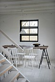 Simple dining area with white-painted chairs around wooden table on metal trestles