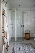 Glass shower cubicle in bathroom with white-tiled walls