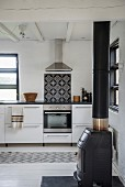 Cast iron log burner in simple kitchen with vintage tiled splashback above cooker integrated in kitchen counter