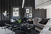 Wassily chair and black and white sofa in masculine interior with arrangement of framed pictures on grey and black striped wallpaper