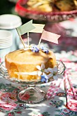 Kuchen mit Papierfähnchen und Essblüten dekoriert auf Kuchenständer