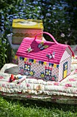 Colourful, house-shaped sewing box on floral floor cushion in garden