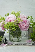 Peonies and lady's mantle in glass jug