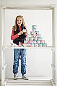 Girl stood next to Advent calender hand-made from decorated tin cans