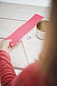 Blechdose, Aufkleber und rosafarbenes Papier in Mädchenhand für DIY-Adventskaldender