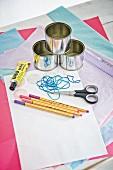 Bastelutensilien für Adventskalender aus Blechdosen, Aufkleber, Gummibändern und Seidenpapier