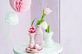 Tulips in vases wrapped in cord next to plate of pink macarons