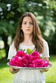 Mädchen hält Tablett mit pinkfarbenen Rosen