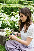 Girl cutting white roses in garden