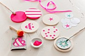 Hand-painted round wooden coasters and painting utensils