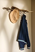 Straw hat and jacket hanging from coat rack hooks