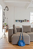 Blue bag next to grey sofa in urban loft apartment