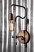 Retro industrial-style sconce lamp on corrugated metal wall