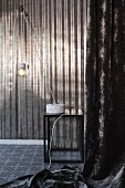 Pendant table lamp with marble base on side table in front of shiny metal wall