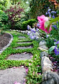 Stone garden path with grass between flags and flowerbed edged with pebbles