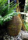 Korb in Vasenform auf Kies neben Farn im Garten