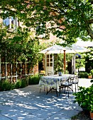 Shady dining area below parasol on terrace outside country house with roses climbing on brick façade