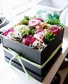 Schwarze Geschenkbox mit Büten dekorativ ausgestaltet