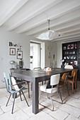 Verschiedene Retrostühle um grauen Tisch in Esszimmer mit weisser Holzbalkendecke