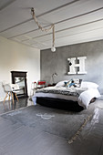 Fur blanket on bed below decorative letter on grey stucco lustro wall in bedroom with grey wooden floor and rug