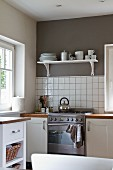 Bright, pleasant kitchen with mushroom-grey wall above white tiled splashback