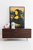 Modified painting of Mona Lisa, bird-shaped table lamp and vases below glass cover on top of sideboard