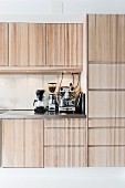 Fitted kitchen with pale wooden fronts, espresso machine, coffee mill and percolator on worksurface
