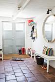 Hauseingang in umgebauter Scheune mit Terrakottaboden, weisse Garderobenbank vor rundem Wandspiegel
