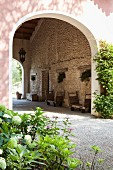 Traditional wooden trolleys against stone wall under covered entrance to Mediterranean country house