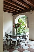 Chairs around glass table on marble floor in front of archway with view of garden