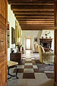Blick durch offene Tür in Loungebereich mit rustikaler Holzbalkendecke und Schachbrettmusterboden
