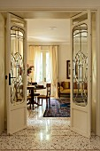 Open Art-Nouveau double doors with glass panels and view into elegant interior with exotic-wood furniture