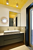 Minimalist designer bathroom with porthole window and wooden ceiling