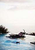 Bequeme Holzliege neben Infinity Pool mit Blick aufs Meer