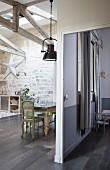 Antike Stühle um Tisch und Industrie-Pendelleuchte neben Durchgang in Loftwohnung mit Edelholzparkett und Natursteinwand