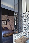 Ornamental wall-tiles in bathroom and view of double bed in bedroom