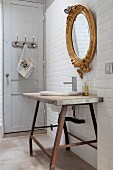 Rustic washstand below gilt-framed mirror on white-tiled wall